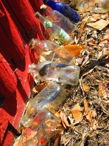 """Found under shingle pile: lots of cool old milk and other bottles. Also, an 8"""" chef's knife, dish drainer, colander, veggie chopper, etc. Basically, contents of kitchen."""