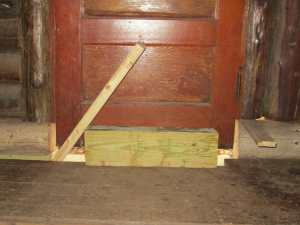 """And we put in the crummy old door, which still fit! Except that there's a giant hole at the bottom and the jamb is partially cut out. This will have to do for a """"lock"""" for now."""